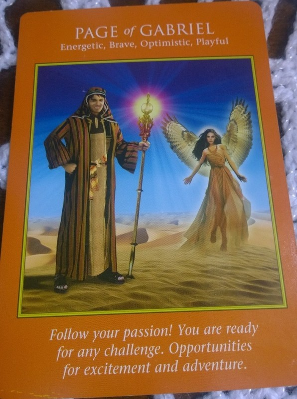 'Page of Gabriel' orange tarot card showing a smiling young strong hero carrying a light bearing staff, supported by archangel gabriel. In the desert under clear blue skies. Text below the image reads 'Follow your passion! You are ready for any challenge.  Opportunities for excitement and adventure.'